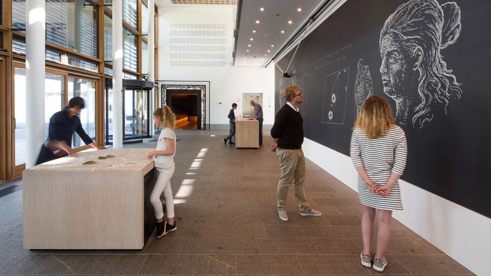 Eingangsbereich Experience Center Royal Jelling mit Empfangstresen und Modelltisch sowie Tafel mit Roboter